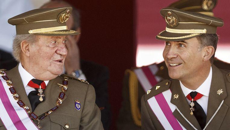 Koning Juan Carlos en zijn zoon kroonprins Felipe vandaag bij een militaire ceremonie in San Lorenzo. Beeld ap