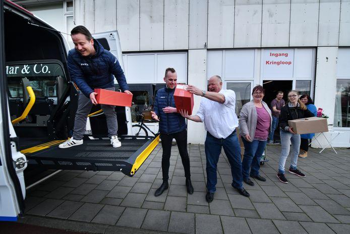 Medewerkers van vervoersbedrijf Brookhuis en Kringloop Help Anderen pakken twee rolstoelbussen vol met etenswaren. In het witte shirt chauffeur Erwin Leis.