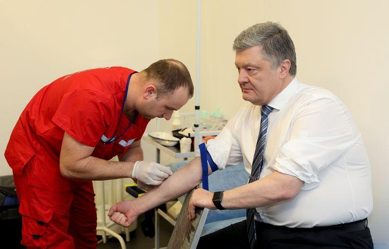 President Petro Porosjenko ondergaat vrijdag een bloedtest in Kiev nadat hij daartoe was uitgedaagd door zijn tegenstander in de verkeizingen, Volodymyr Zelensky. Beeld AP