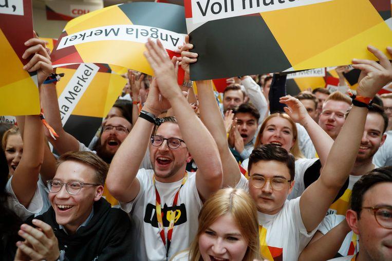Supporters van de CDU juichen nadat de resultaten binnenlopen. Merkels partij wint de verkiezingen, maar het lastige werk begint nu, met de coalitievorming. Beeld AFP