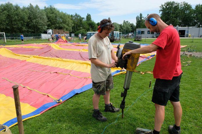 Vrijwilligers zijn druk in de weer om de tent op te zetten.