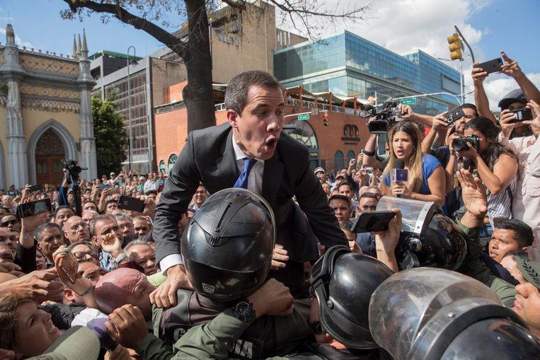 Venezolaanse ordetroepen proberen oppositieleider Juan Guaidó tegen te houden als hij dinsdag het parlementsgebouw in Caracas probeert binnen te komen. De politie moest uiteindelijk wijken, waarna de parlementariërs Guaidó opnieuw aanwezen als parlementsvoorzitter en interim-president. Beeld EPA