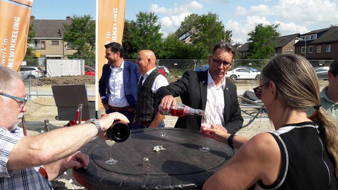 Wethouder Frank van Hulle (rechts) schenkt de champagneglazen vol bij start nieuwbouw Madame Curiehof, achter hem Clavis-directeur Ruben Karel en Van der Poel-directeur Kees de Regt (vlnr).