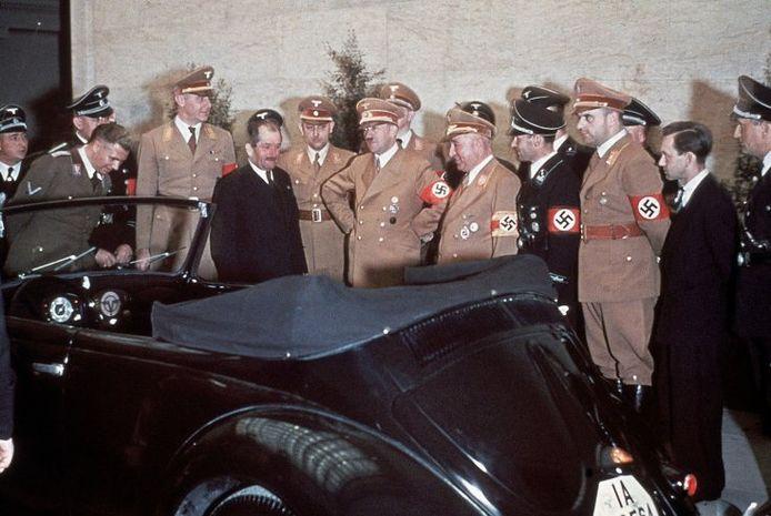 Ferdinand Porsche (links in kostuum) en Adolf Hitler bewonderen  de cabriolet die Hitler als verjaardagscadeau kreeg
