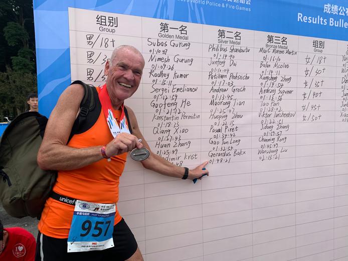 Gerard Baxk met zijn zilveren medaille. Gewonnen op de halve marathon in de leeftijdscategorie 65+. Bakx is oud-directeur van de Rotterdamse penitentiaire inrichtingen.