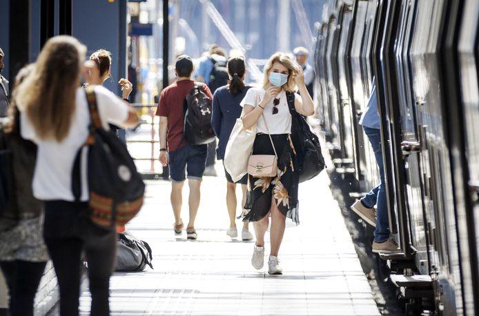 Reizigers met mondkapjes op Amsterdam CS.