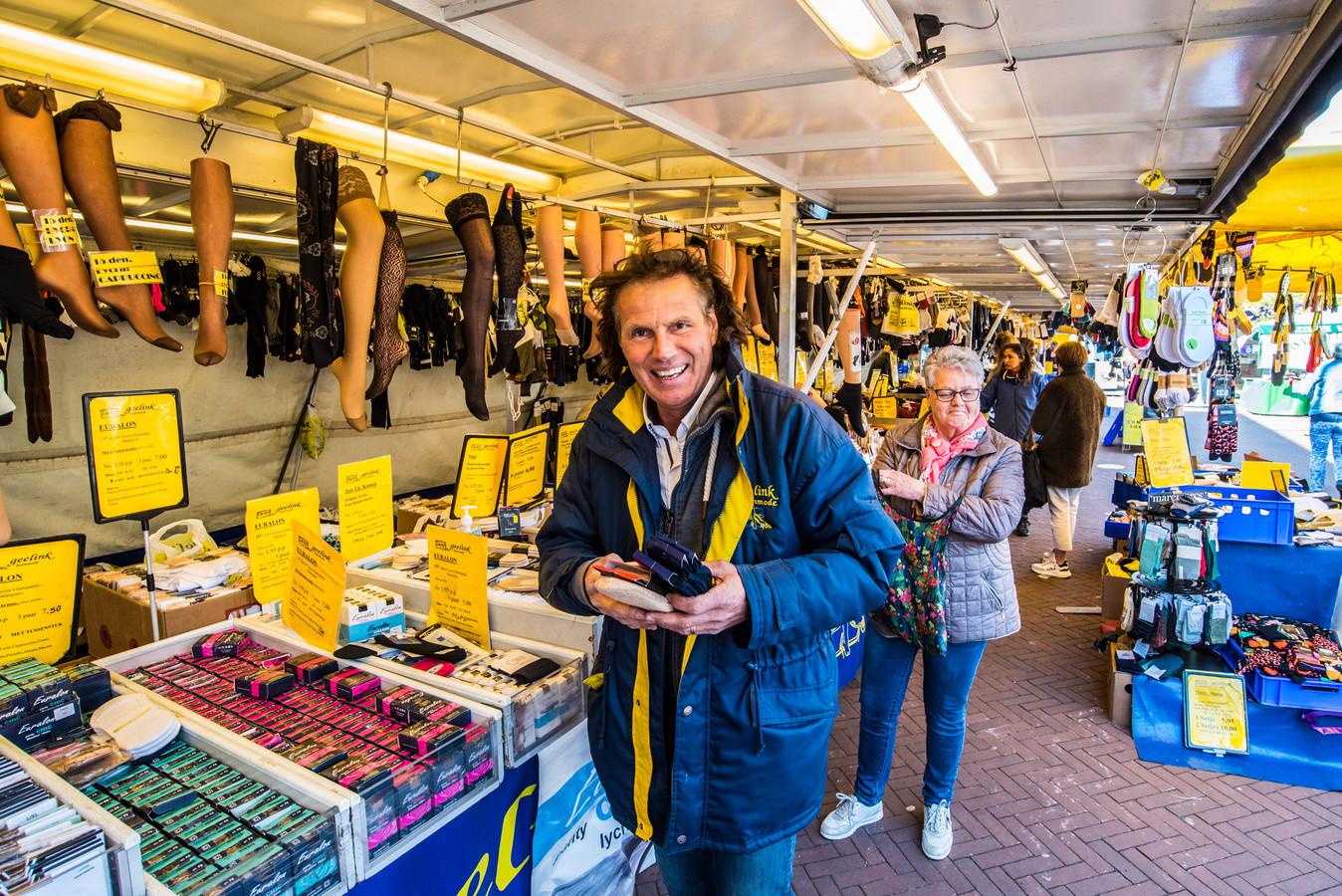 Ben Geelink lacht omdat hij eindelijk weer zijn sokken en panty's kan verkopen. Een enkele vaste klanten trakteert hij zelfs op bloemen.