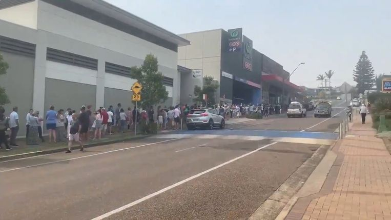 Mensen staan buiten in de rij voor een supermarkt. Beeld Mick Meredith /via REUTERS