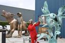 Kunstenares Margot Berkman bezig met het patineren van een sculptuur. De Waterwolf en de Aquanaut krijgen een soortgelijke kleur.