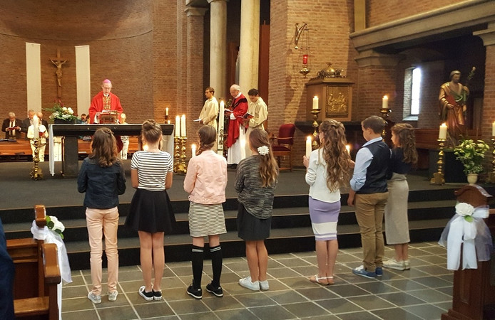 7 vormelingen luisteren aandacht naar bisschop De Korte, bijgestaan door pastoor Van der Vinne en 2 misdienaars