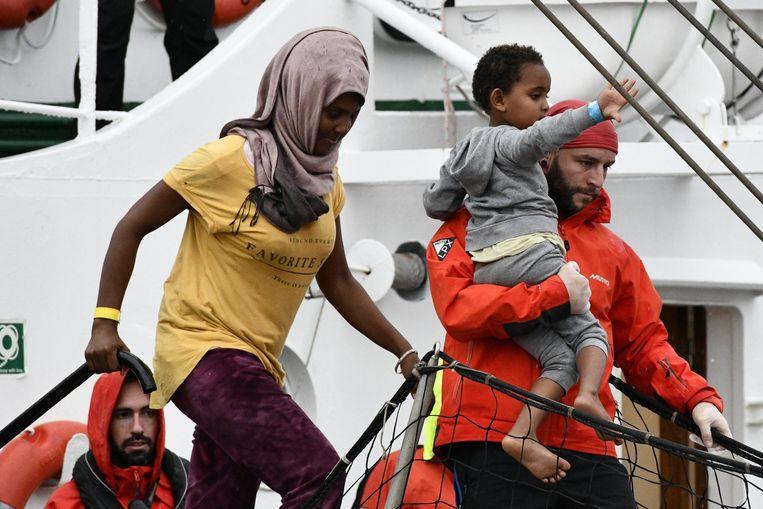 Een groep migranten, onder wie jonge kinderen, komt aan in Italië. Beeld Photo News