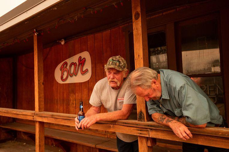 Dave Ferner (l.) en Bob Prary (r.) kijken toe hoe de bosbrand voorbij hun stadje Doyle, Californië, raast. Prary verloor zijn woning vorig jaar in een bosbrand. Beeld AP