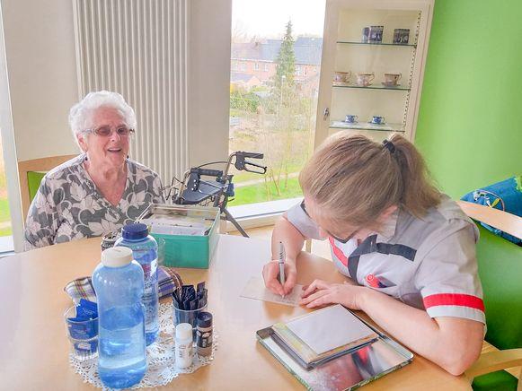 Een medewerkster schrijft samen met een bewoonster van De Gerda een briefje naar de familie.