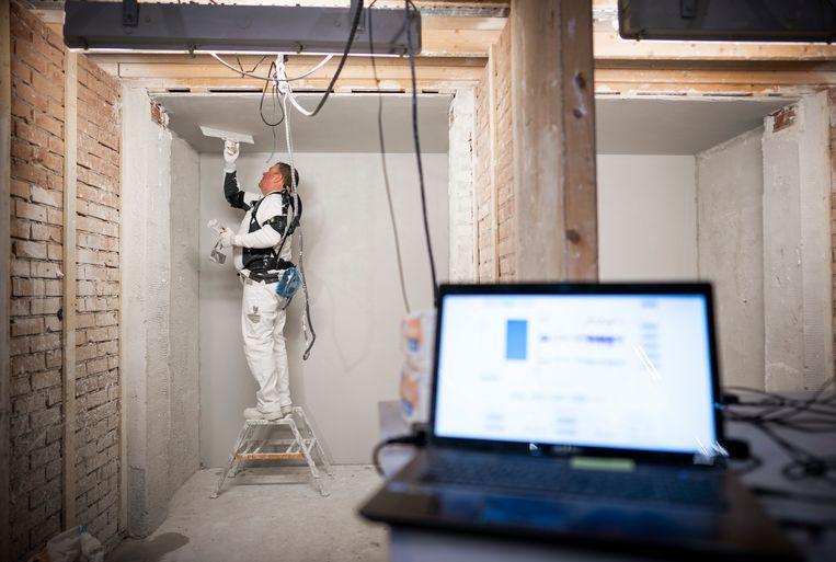 Een stukadoor aan het werk met een exoskelet in een testomgeving in Veenendaal. Rechts laptops met gegevens die gemeten worden.  Beeld Freek van den Bergh