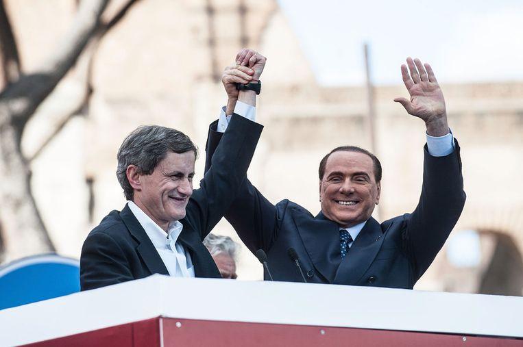 Oud-premier Silvio Berlusconi (rechts) en de door hem gesteunde burgemeester van Rome, Gianni Alemanno. Beeld getty