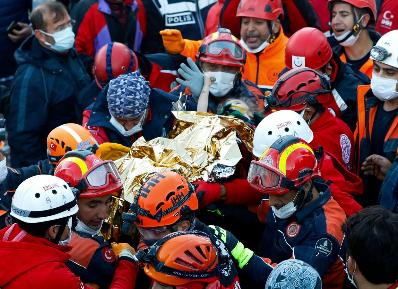 Deze foto van een kluwen reddingswerkers die het 3-jarige meisje Elif uit het puin van een ingestort flatgebouw in Izmir draagt, ding de wereld over.  Beeld AP