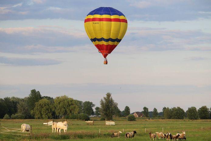 Een luchtballon vliegt over weilanden. Deze luchtballon is niet de ballon uit het verhaal.