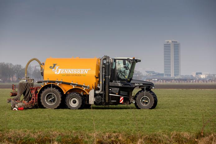 Een boer rijdt mest uit; op de achtergrond het provinciehuis in Den Bosch.