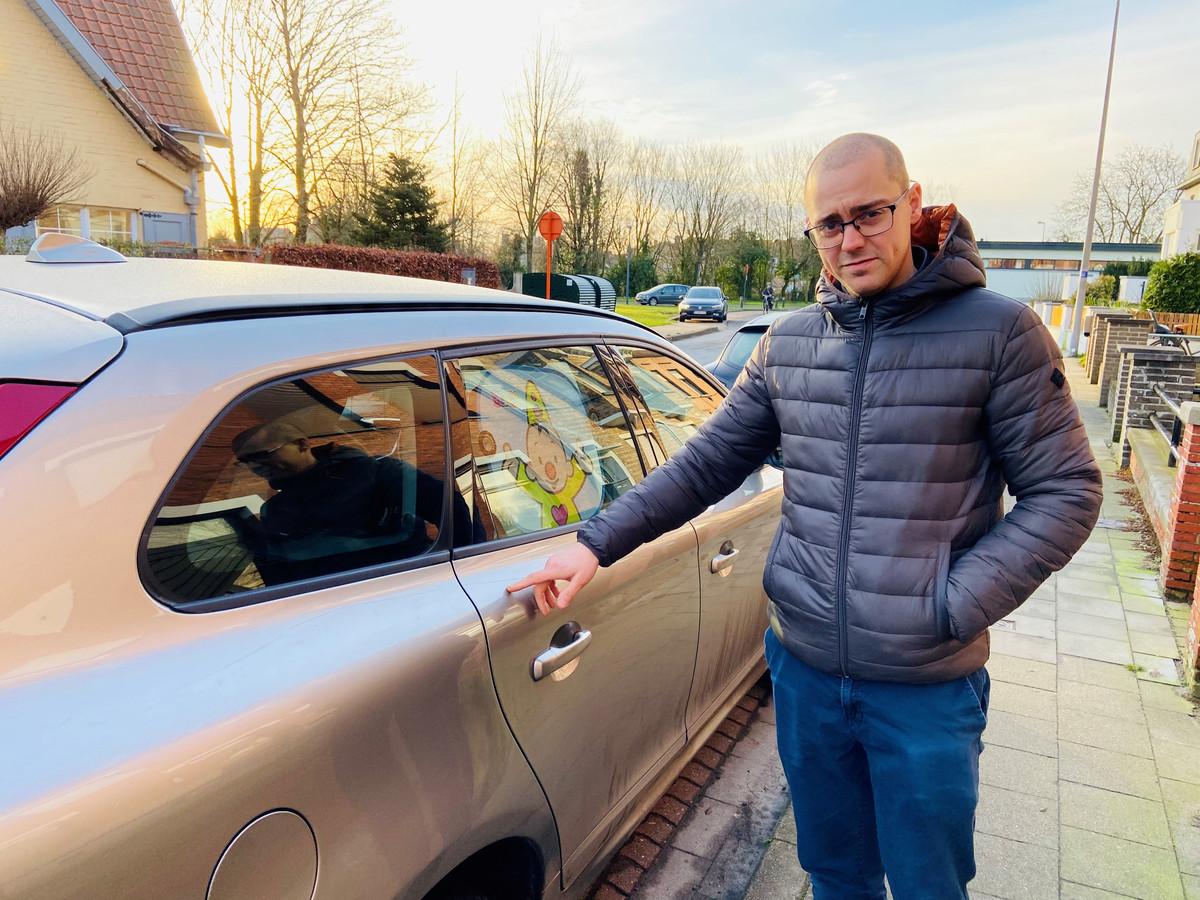Jonas Bostoen bij z'n beschadigde Volvo, een van de vele doelwitten van de vandaal.