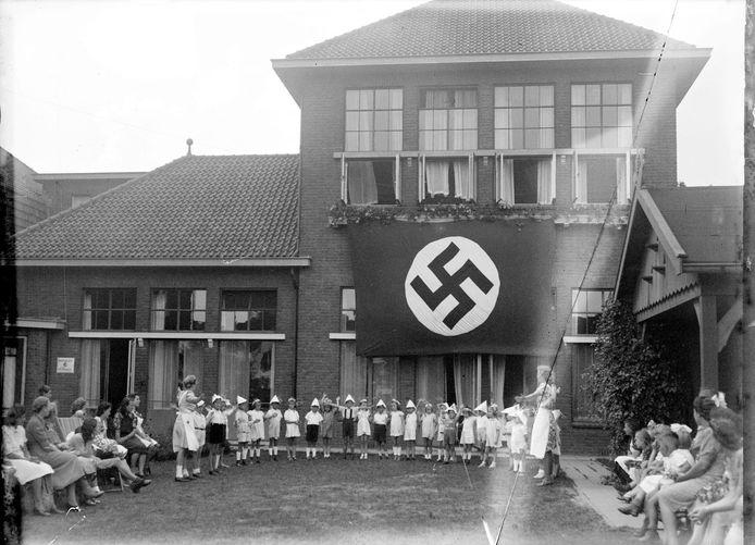 Spelende kinderen onder een nazivlag aan de gevel van de Nutsschool, de huidige L.W. Beekmanschool in Den Bosch.