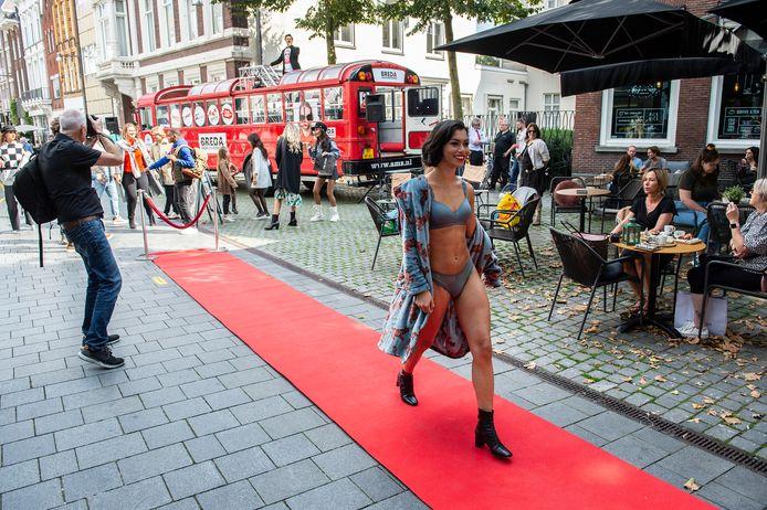 Het vijfde Breda Fashion Weekend in de binnenstad. Op verschillende locaties in de stad zoals hier in de Veemarktstraat, presenteren verschillende Bredase kledingwinkels gezamenlijk een modeshow. De modellen verplaatsen zich in een rode bus.