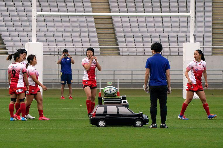 Gemak dient de mens, ook in het vrouwenrugby. Tijdens een testwedstrijd ter voorbereiding op de Olympische Spelen in Tokio, brengt een op afstand bestuurbare auto de bal naar het veld van het olympisch stadion. De met een jaar uitgestelde Spelen beginnen 23 juli. Beeld EPA