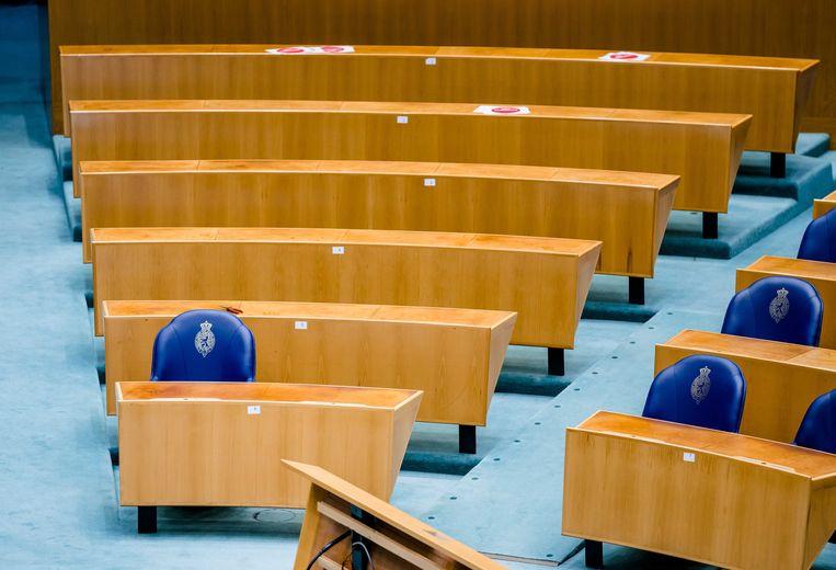 De stoelen van de Tweede Kamerleden worden gedemonteerd voor de verhuizing. Beeld ANP