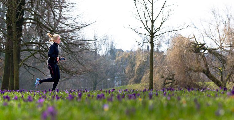 Een jogger loopt alleen door het Amsterdamse Vondelpark, een wedstrijdje zit er voorlopig niet in.  Beeld   ANP