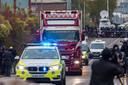 De vrachtwagen waarin gisteren 39 lichamen werden gevonden, wordt onder politiebegeleiding afgevoerd voor verder onderzoek.