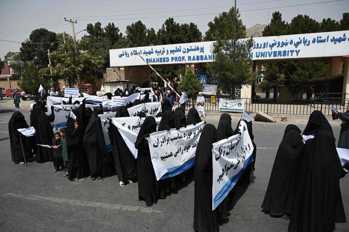 Des femmes voilées tiennent des banderoles et des pancartes lors d'un rassemblement pro-taliban devant l'université d'éducation Shaheed Rabbani à Kaboul, le 11 septembre 2021.