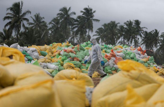 Een lid van de Sri Lankaanse marine wandelt voorbij afvalzakken vol met troep die was aangespoeld op de stranden.