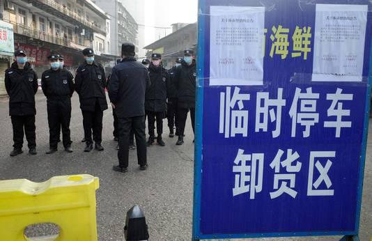 Beveiligers bij de momenteel gesloten vismarkt in Wuhan waar de eerste mensen besmet raakten