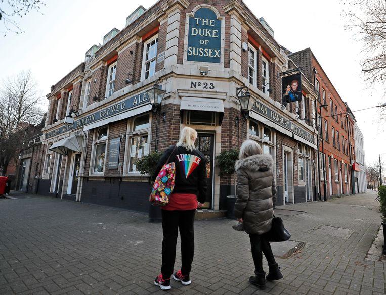 Mensen kijken naar de afbeelding van de veelbesproken Harry en Meghan bij een pub nabij treinstation Waterloo in Londen.   Beeld AP
