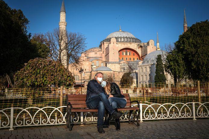 Mensen met mondmasker genieten van de zon op een bankje in Istanboel.