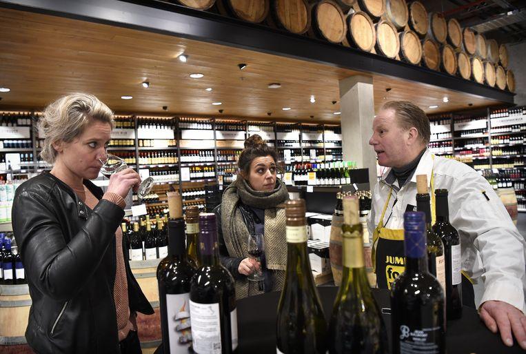 Bij de Jumbo Foodmarkt in Leidsche Rijn geeft een Jumbo-medewerker twee klanten uitleg over diverse soorten wijn.  Beeld Marcel van den Bergh
