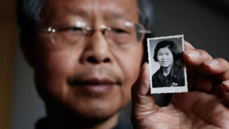 Zhang Hongbing laat een foto van zijn moeder Fang  zien, die op 11 april 1970 in het openbaar werd terechtgesteld. Beeld The Guardian