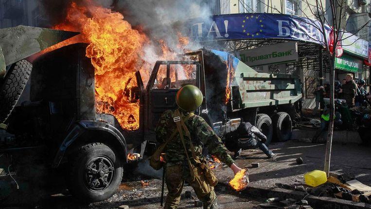 Demonstranten hebben in Kiev militaire voertuigen in de fik gestoken. Beeld REUTERS
