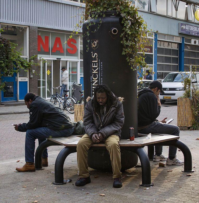 Voor de ingang van de Nico Adriaans Stichting (NAS) in Rotterdam zit een aantal mannen op een bankje. De heren komen niet voor in het verhaal. Beeld Arie Kievit