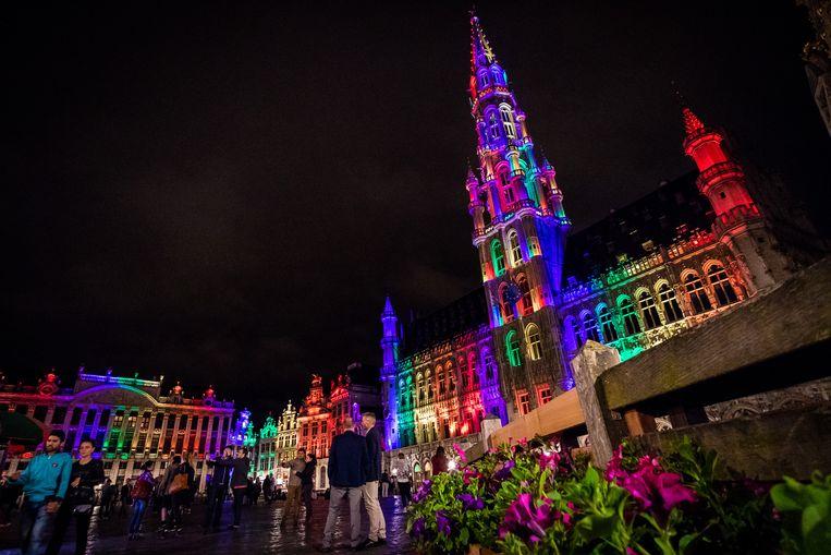 Het Brusselse stadhuis en de andere gebouwen op de Grote Markt, verlicht in de regenboogkleuren. Beeld BELGA