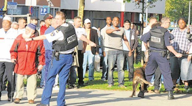 Buurtbewoners in de Strijensestraat in Rotterdam waar de schietpartij plaatsvond. FOTO OLIVIER VAN DET