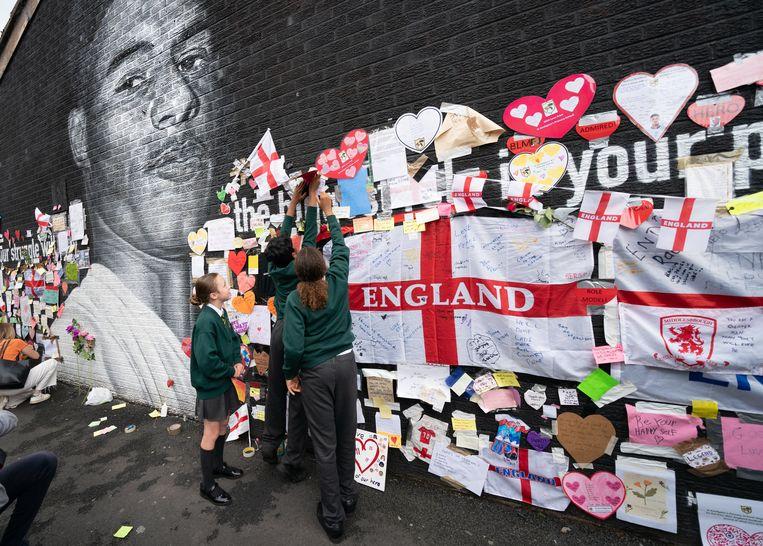 De muurschildering van Rashford werd inmiddels in ere hersteld, terwijl buurtbewoners voor boodschappen van liefde zorgden. Beeld Photo News