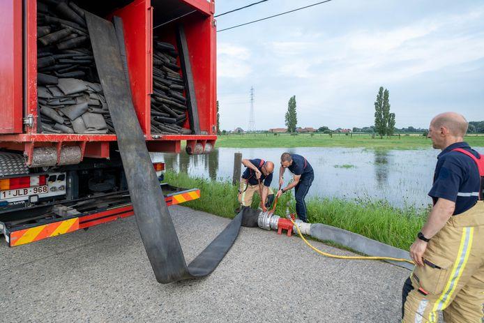 De brandweer pompt water uit een veld en een beek in de Tiendenschuurstraat weg