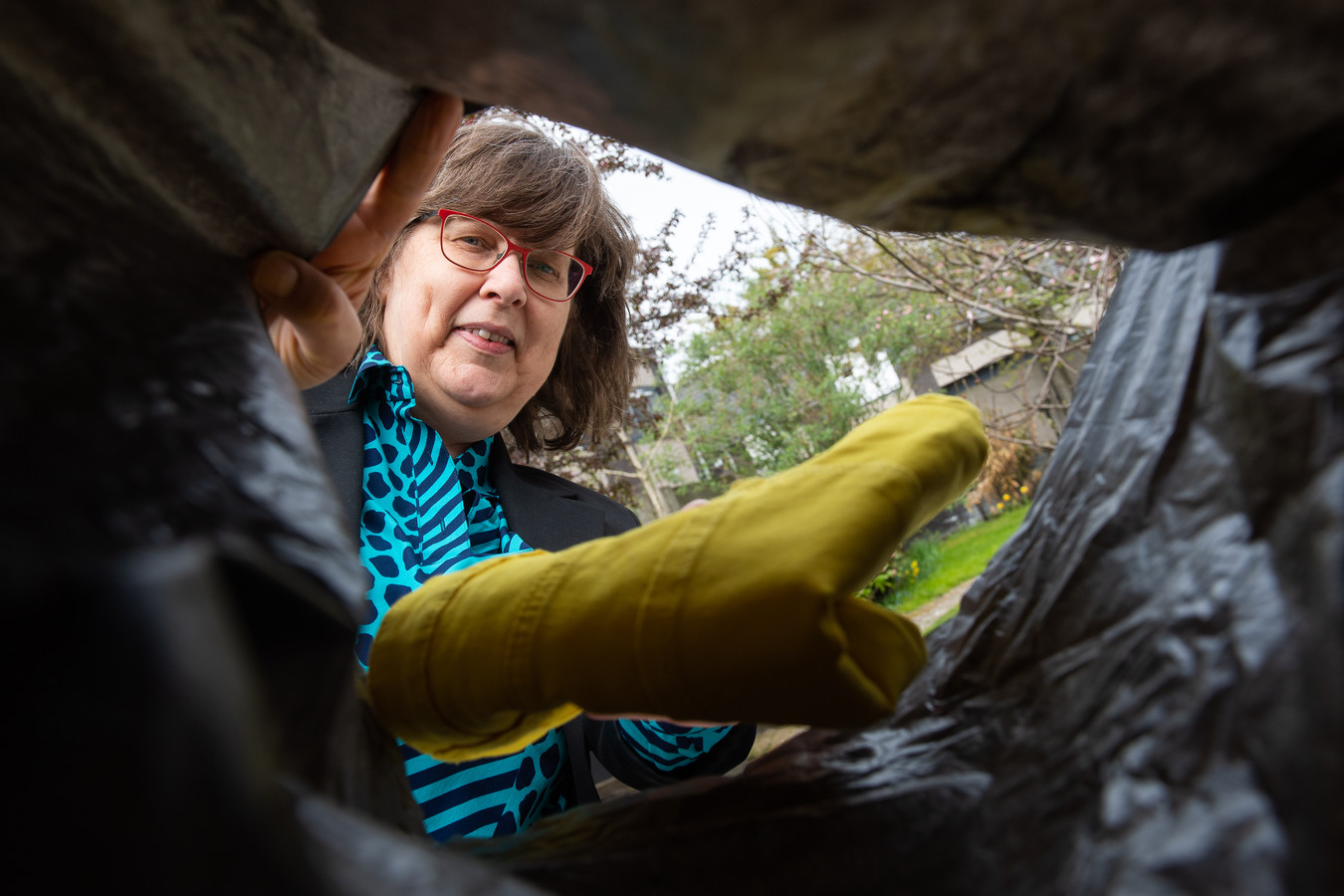 Made - Pix4Profs/René Schotanus. Carla van der Velden stopt kleding die weg mag in een tas voor haar project.