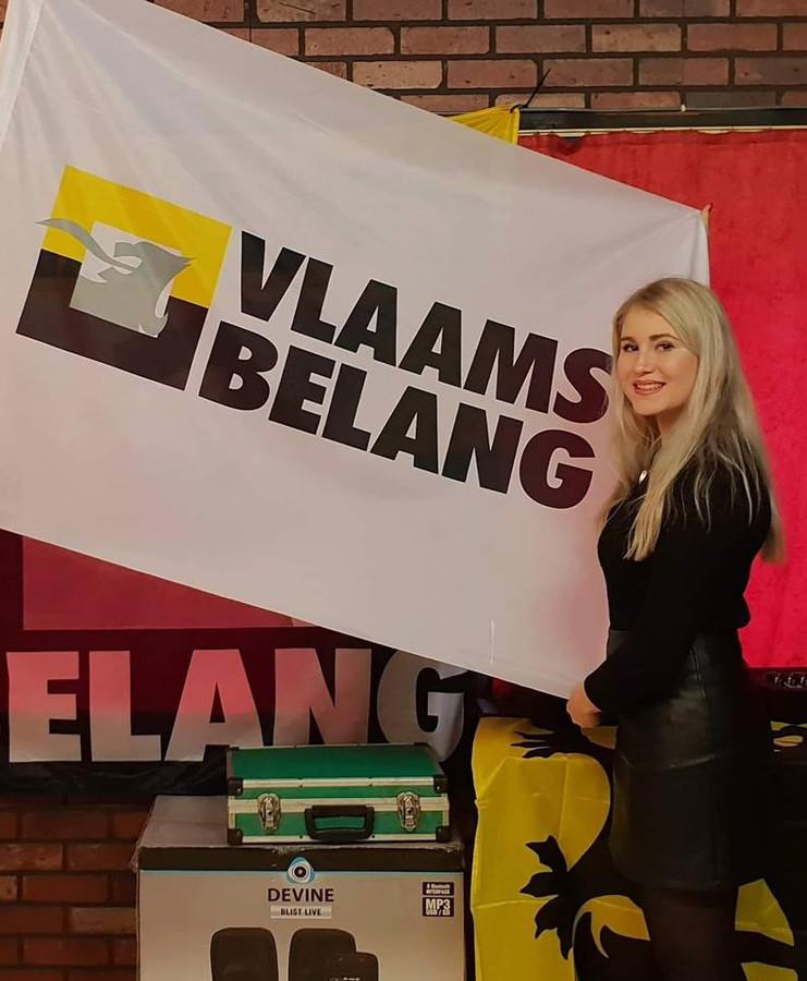 Carrera Neefs bij een vlag van Vlaams Belang.