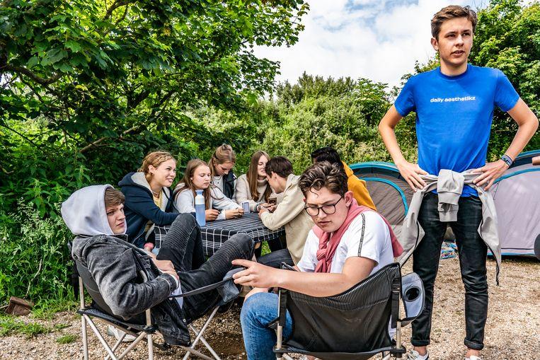 De vriendenclub op camping De Lakens. Staand rechts Julian en vooraan zittend op de stoel Thijmen (met bril). Beeld Joris van Gennip