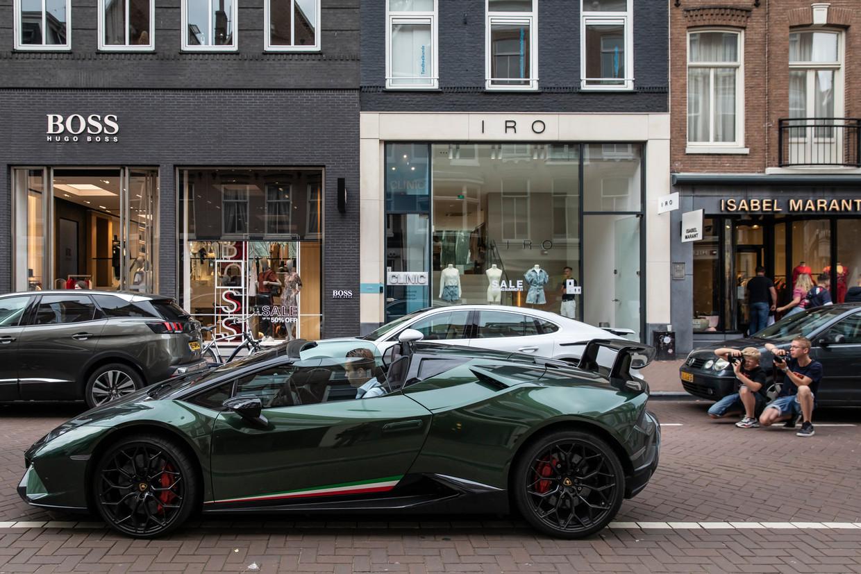 Jonge jongens fotograferen luxe auto's in de P.C. Hooftstraat. Beeld Dingena Mol