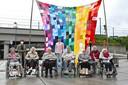 Schepen Hostekint, Mister Gay Belgium 2017 Jamie Deblieck en Deniza Miftari samen met enkele bewoners van de Roeselaarse woonzorgcentra die een steentje bijdroegen bij het maken van de indrukwekkende  regenboogvlag.