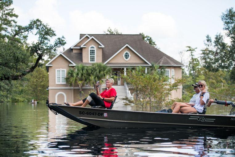 Mensen in Conway, South Carolina manoeuvreren hun boot door het overstromingsgebied rond de Waccamaw River. Beeld null