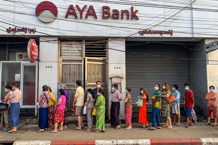 Myanmarezen in de rij voor de bank. Beeld AFP