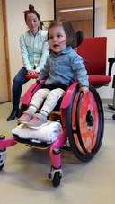 Emine kijkt toe hoe Sara voor het eerst oefent in een rolstoel.